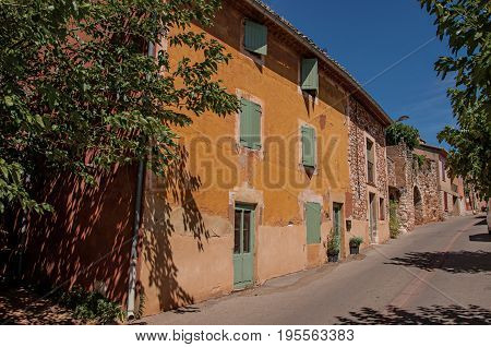 Roussillon, France - July 03, 2016. Traditional colorful houses in ocher and blue sky in the historic city center of Roussillon. In the Vaucluse department, Provence region, southeastern France