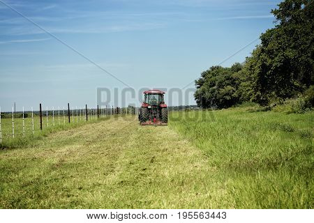 Farming: Large red tractor moving green farmers pasture