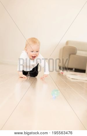 Nicely Dressed And Happy Baby Girl With Blue Eyes Crawling On The Ground. Playing With Ball.