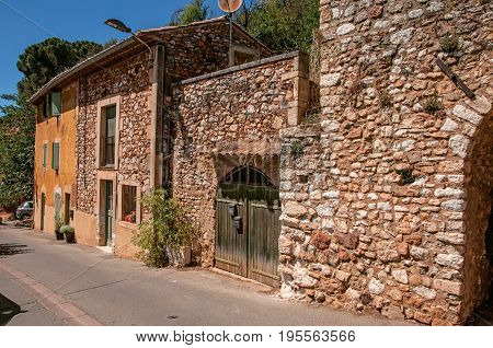View of traditional colorful houses in ocher under a sunny blue sky, in the city center of the village of Roussillon. Located in the Vaucluse department, Provence region, southeastern France