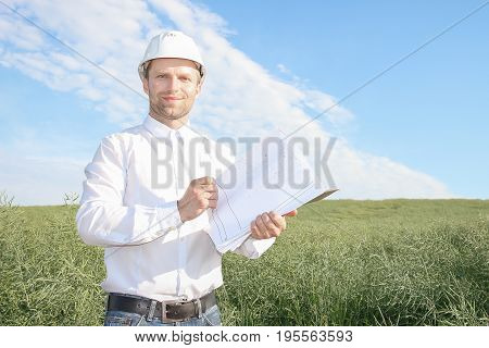 Happy working architect in white helmet with documentation smiling. Handsome young man at work. Concept of trade unions and workers organizations. A professional or  technical specialist.