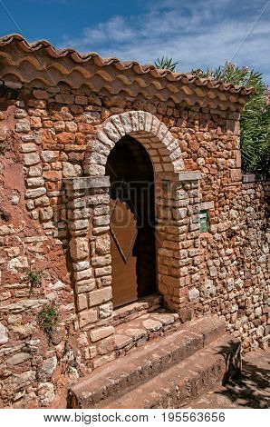 View of wooden door and wall and arch in stone under a sunny blue sky, in the city center of the village of Roussillon. Located in the Vaucluse department, Provence region, southeastern France