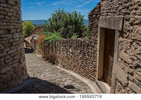 View of typical stone houses and wall with sunny blue sky, in alley of the historical city center of Gordes. Located in the Vaucluse department, Provence region, southeastern France