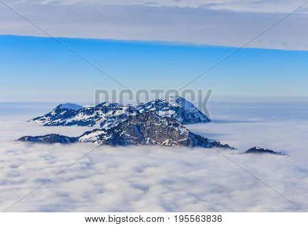 Summits of the Swiss Alps rising from a sea of fog - wintertime evening view from the Fronalpstock mountain in the Swiss canton of Schwyz. The furthermost summit with a telecommunication tower on it belongs to well-known Mt. Rigi.
