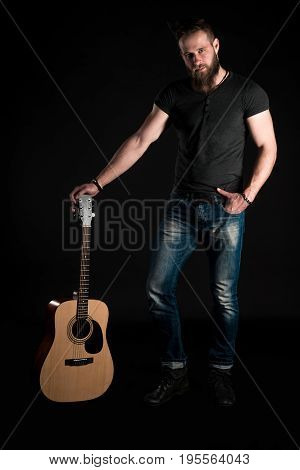 A Charismatic And Stylish Man With A Beard Stands Full-length With An Acoustic Guitar On A Black Iso