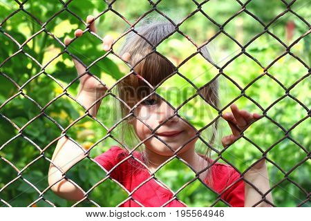 Abstract picture of a little girl behind chain link fence. Photo combination concept