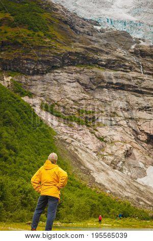 Adventure hiking man admiring Boyabreen Glacier in Fjaerland area Sogndal Municipality in Sogn og Fjordane county Norway. Tourist visiting norwegian nature landscape.