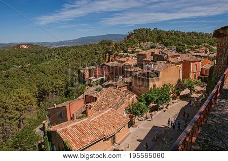 Panoramic view of the fields and hills of Provence from the city center of Roussillon, with stone houses, roofs and trees in the foreground. Vaucluse department, Provence region, southeastern France.