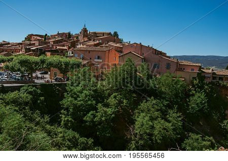 Panoramic view of the village of Roussillon and surrounding woods, under a sunny blue sky. Located in the Vaucluse department, Provence region, in southeastern France