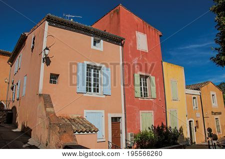 View of traditional colorful houses in ocher under a sunny blue sky, in the city center of the village of Roussillon. Located in the Vaucluse department, Provence region, in southeastern France