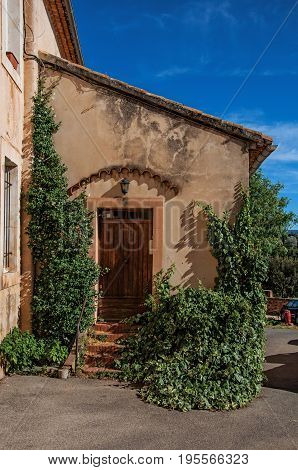 View of traditional colorful house in ocher and bindweed under a sunny blue sky, in the city center of Roussillon village. Located in the Vaucluse department, Provence region, southeastern France
