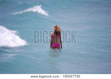 young woman wearing pink bikini wading in the ocean before wave hits her.