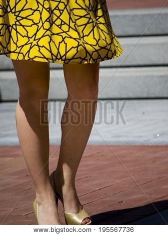 Young woman shown from waist down wearing a yellow dress black print as she walks though Sundance Square Ft Worth TX