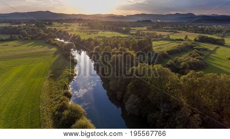 Aerial view of river bending across fields at sunset. Ljubljanica running through marshes, Slovenia.