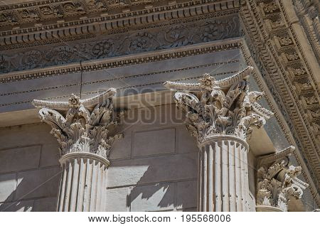Close-up of decorative capital and frieze on the Maison Carrée's columns, an ancient Roman temple, in the city center of Nimes. Located in the Gard department, Occitanie region in southern France