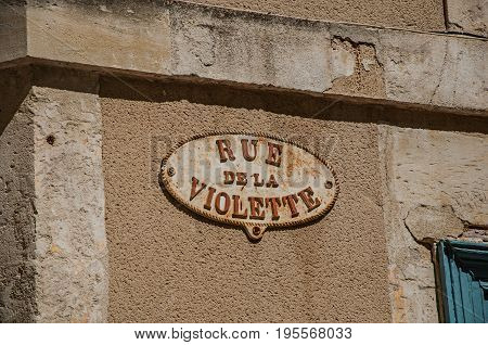 Close-up of street sign board with sunny blue sky in the city center of Nimes. Located in the Gard department, Occitanie region in southern France