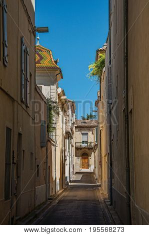View of a narrow alley with sunny blue sky, in the city center of Nimes. Located in the Gard department, Occitanie region in southern France