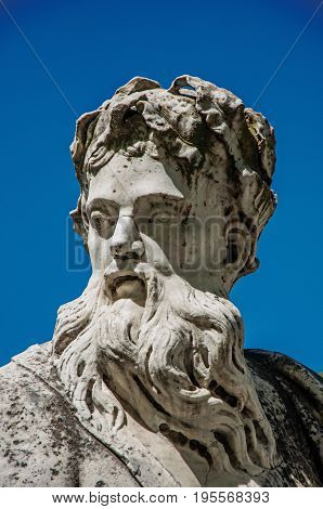 Close-up of a statue at the Gardens of the Fountain and a sunny blue sky, in the city center of Nimes. Located in the Gard department, Occitanie region in southern France