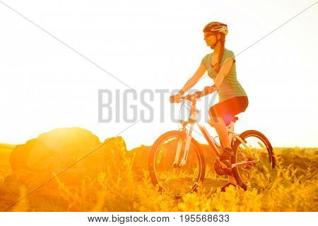 Young Woman Riding the Mountain Bike on the Summer Rocky Trail at Beautiful Sunset. Travel, Sports and Adventure Concept.