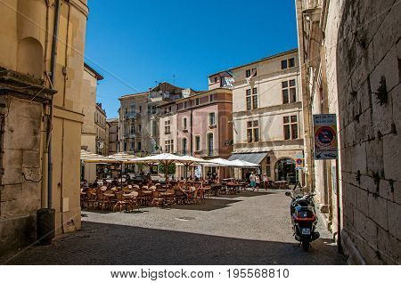 Nimes, France - July 04, 2016. Square with restaurants, buildings and blue sky in city center of the ancient town of Nimes. Located in the Gard department, Occitanie region, southern France