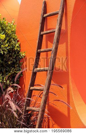 Rustic wooden ladder against a bright orange wall in summer