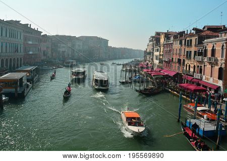 Venice Italy,October 16th 2013.The Grand Canal of Venice is always a busy place with gondolas delivery boats and tourist Vaporetto's .Taken from the famous Rialto bridge showing fine restaurants and awesome hotels.Come to this romantic city of Venice and