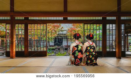 Japanese Geisha Look At A Small Rock Garden At  Kennin-ji Temple In Colorful Autumn