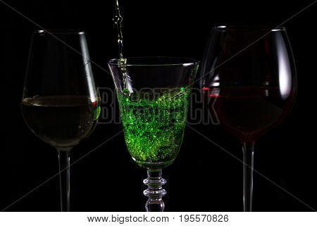 Beautiful splash of green cocktail on a black background
