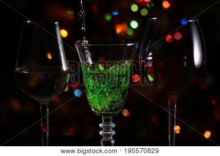 Beautiful splash of green cocktail on the background of festive lights