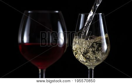 Beautiful splash of wine in a glass on a black background