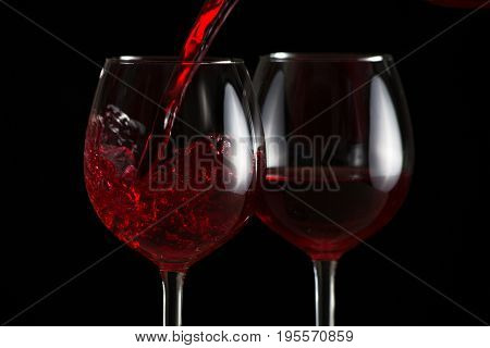 Beautiful splash of red wine in a glass on a black background