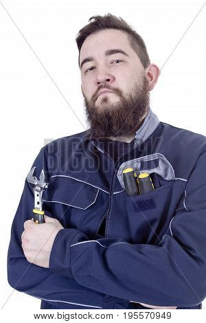Bearded young man with a wrench in a working overall