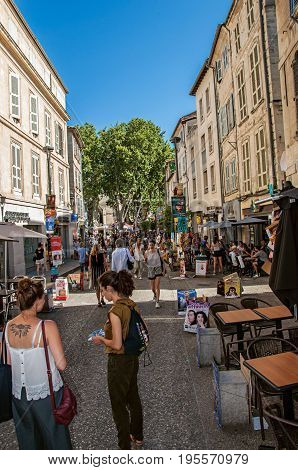 Avignon, France - July 06, 2016. People strolling and having fun under a sunny blue sky in the city center of the charming Avignon. In the Vaucluse department, Provence region, southeastern France