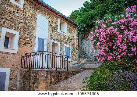 Chateauneuf-de-Gadagne, France - July 06, 2016. View of stone house, staircase and flowers in the historical city center of Châteauneuf-de-Gadagne. Vaucluse department, Provence region, southeastern France