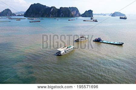 Halong Bay, Vietnam. Limestone Islands with cloudy sky. Freighters and Boats