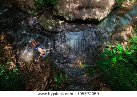 Top view boy are soaking the stream from the stream that flows down the mountain happily with nature Dark tones