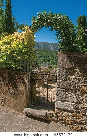 Ménerbes, France - July 07, 2016. View of small garden behind iron gate and stone wall in the village of Ménerbes. Vaucluse department, Provence region, southeastern France