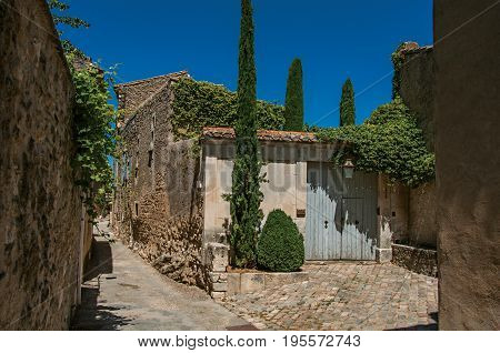 Ménerbes, France - July 07, 2016. View of typical stone house with garage door, in an alley of the historical village of Ménerbes. Vaucluse department, Provence region, southeastern France
