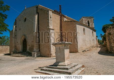 Ménerbes, France - July 07, 2016. Front facade of stone church on a sunny day with foreground cruise, in the historical village of Menerbes. Vaucluse department, Provence region, southeastern France