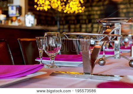 Serving Table In Restaurant With Wine Glasses And Cutlery.