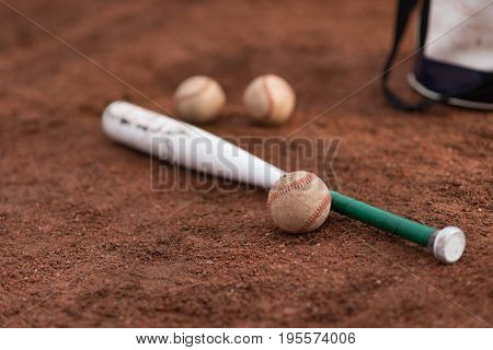 baseball bat and balls and a bag on floor