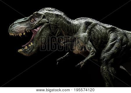 tyrannosaurus toy on a dark background close up