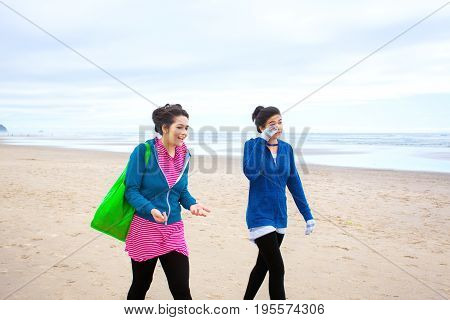 Two biracial Asian Caucasian teenage girls talking while walking along beach on cool cloudy day