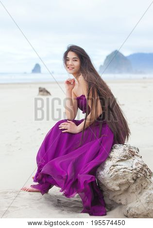 Beautiful biracial Asian Caucasian teenage girl wearing bright purple magenta dress or gown sitting on a rock on beach by ocean with cool cloudy sky