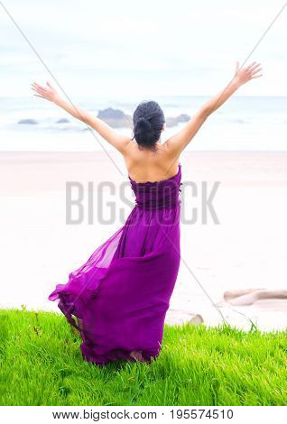 Beautiful biracial Asian Caucasian teen girl wearing purple magenta dress standing on grassy knoll overlooking ocean arms raised