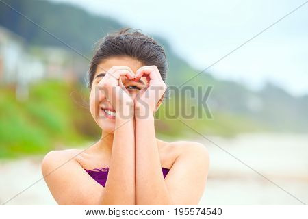 Beautiful biracial teen girl smiling looking through hands formed in heart shape while standing outdoors on beach