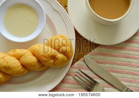 twist bread dipping with sweetened condensed milk and coffee cup