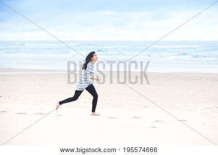 Young biracial teen girl running on beach by ocean