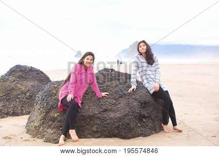 Two biracial Asian Caucasian teen girls sitting on large rock on beach near ocean smiling