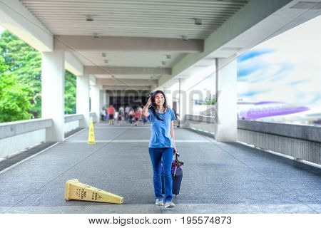 Young teen girl walking along outdoor airport terminal with suitcase